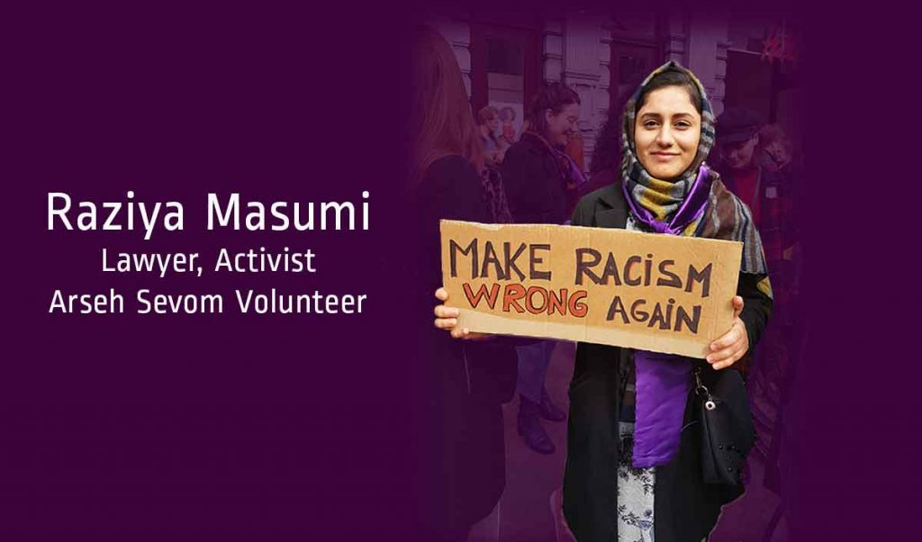 """Young woman wearing a multi-colored scarf and holding a cardboard sign that reads """"Make Racism Wrong Again"""""""