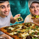 Screenshot of young man and older woman showing us a slice of pizza. Whole pizza in front.